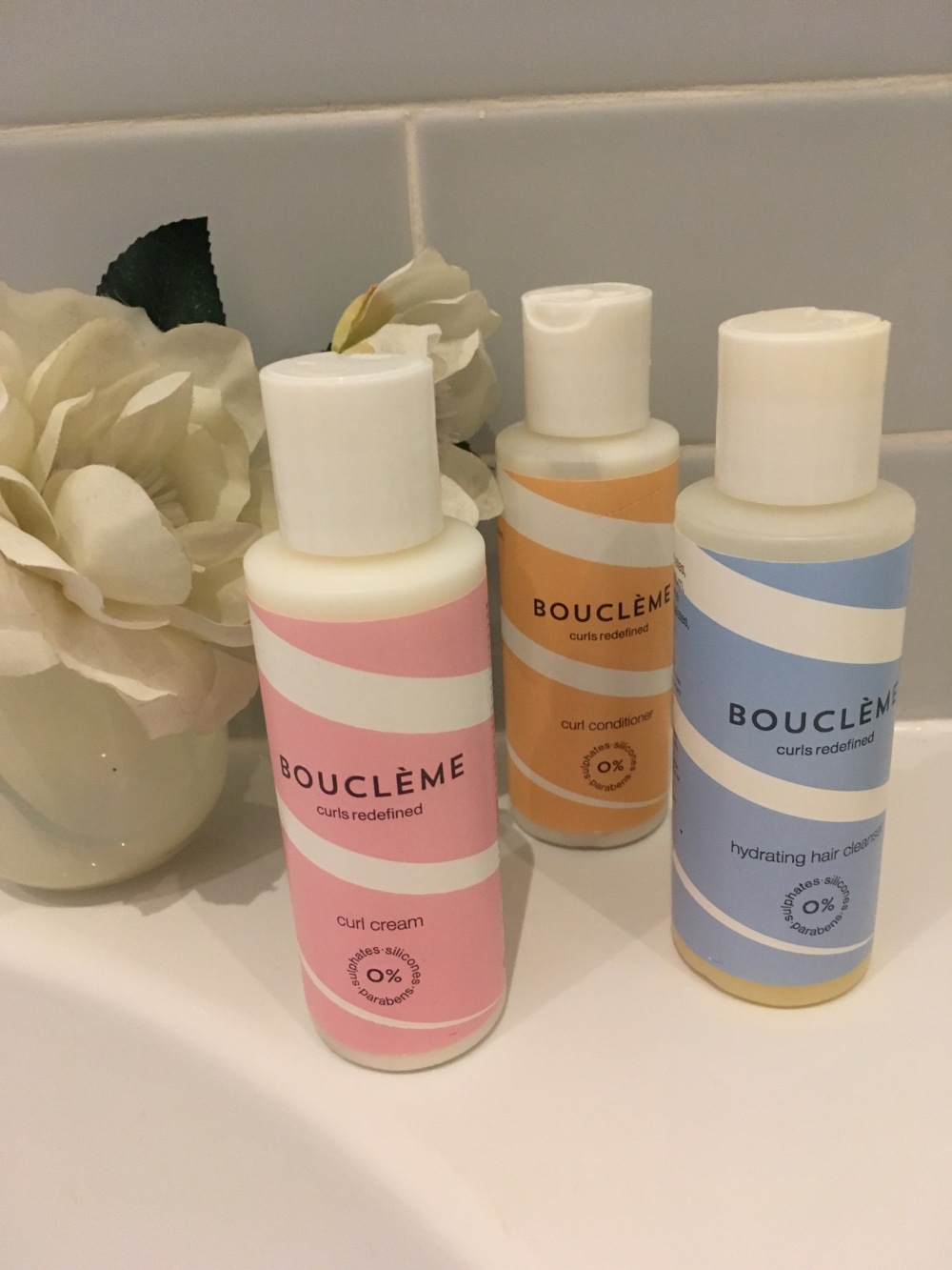 Christmas gift ideas for women. 3 pastel coloured shampoo bottles on the side of a bath with a white silk flower