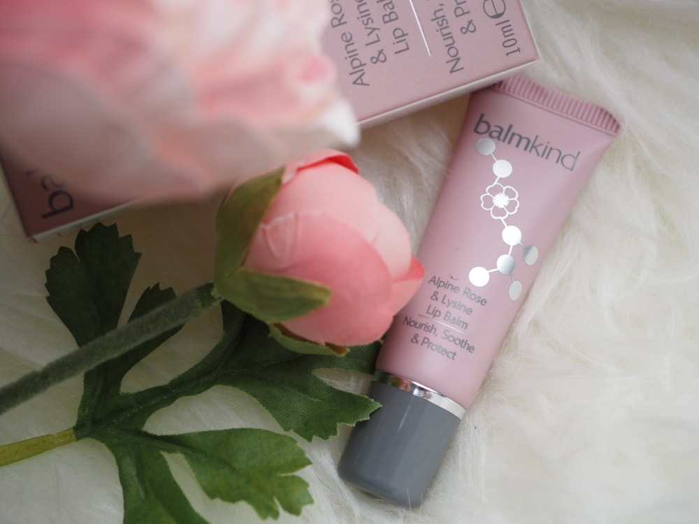 Balmkind Alpine Rose and Lysine Lipbalm- pink tube and box next to flower